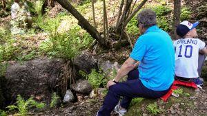 Presidentti Niinistö kuuntelen porun solinaa lasten metsäretkellä.