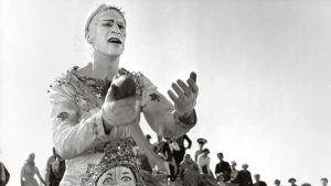 Klovniksi maskeerattu mies seisoo pitäen jotain esinettä kädessään. Väkijoukko takana istuu ja katsoo klovnia.