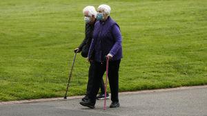Två äldre personer promenerar utomhus i Victoria, Australien. De bär munskydd.