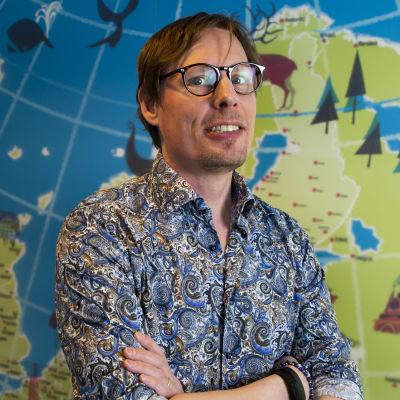 En man med glasögon står med armarna i kors och tittar in i kameran. Han står framför en tavla som föreställer en karta. Han är klädd i en blommig skjorta.