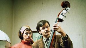 Marja Packalen katsoo, kun Heikki Kinnunen soittaa bassoa.