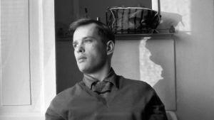 Porträtt på Jörn Donner som sitter i profil så att man ser hans skugga i bakgrunden.