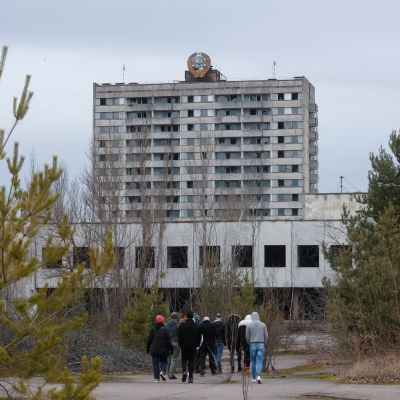 Ihmisjoukko kävelee kohti suurta, neuvostotyylistä rakennusta.