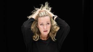 Katariina Kaitueen näyttelemä nainen seisoo mustassa huoneessa mustissa vaatteissa, ja haroo hiuksiaan vakavana.