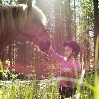 en liten flicka, en häst och en solig dag i skogen