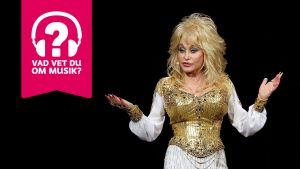 Dolly Parton står med armarna litet usträckta åt sidorna och händerna uppåt.