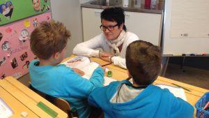 Skolgångshandledare Denise Lönnroth hjälper till med matematikuppgifterna
