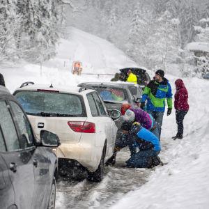 Bilförare sätter på snökedjor nästa Untertauern i Österrike den 7 januari 2019.