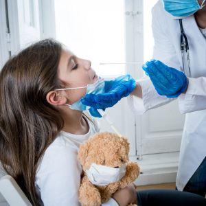 Ett barn testas för coronaviruset. Hon håller i en nalle medan sjukskötaren utför testet.