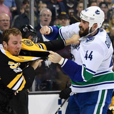 En Canucksspelare slåss mot en Bruinsspelare i NHL.