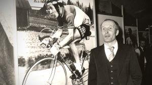 Harry Hannus stående framför en plansch ned honom cyklande
