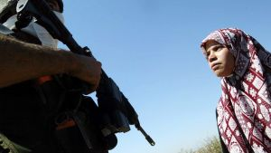 Palestinsk flicka och israelisk soldat i byn Al Zawiya på Västbanken.