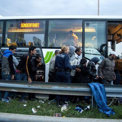 Flyktingar köar för att komma på bussar från Ungern till Österrike
