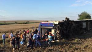 Räddningsarbetare bär iväg offren från en tågolycka i Turkiet.