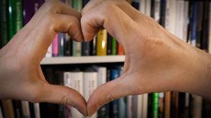 Två händer formar ett hjärta framför en bokhylla.