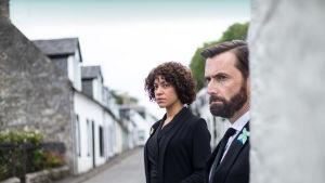 Jess Milner (Cush Jumbo) ja Tom Kendrick (David Tennant) katsovat kulman takaa mietteliään näköisinä.