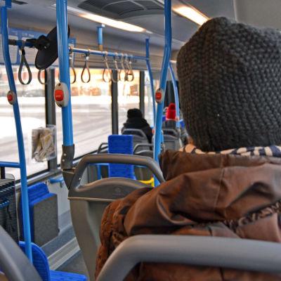 Bild inifrån en stadsbuss. Man ser flera tomma säten och några passagerare.