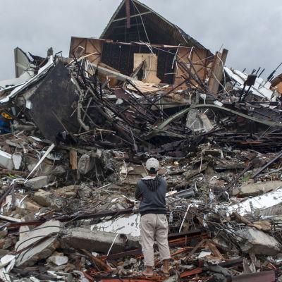 En man står med armarna i kors och tittar på ett hus som rasat ihop i Mamuju, Indonesien.