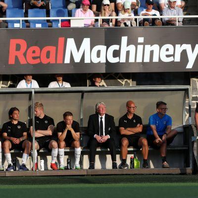 Päävalmentaja Teemu Tainio seisoo FC Hakan vaihtopenkin vieressä.