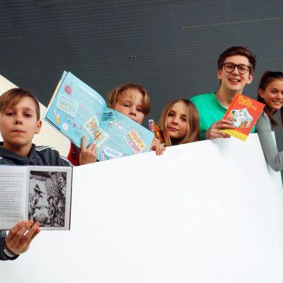 Lapset poseeraavat kirjojen kanssa.