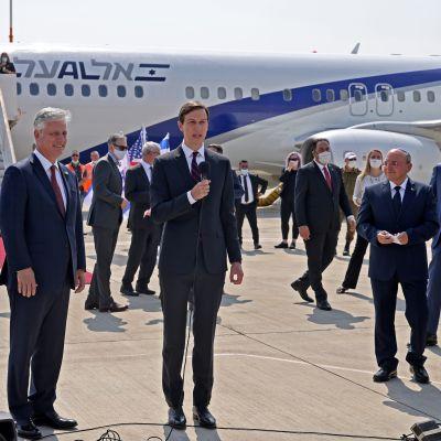 Kushner puhuu mikrofoniin, taustalla lentokone, jonne johtaa punainen matto.