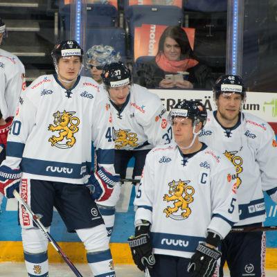 Besvikna finländska landslagsspelare i ishockey pustar ut efter match.
