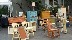 Möbler från olika tidsepoker på en loppmarknad utomhus.