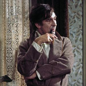 Tupakkatakkiin pukeutunut Sherlock Holmes (Robert Stephens) polttaa piippua mietteliään näköisenä. Kuva elokuvasta Sherlock Holmesin salaisuus