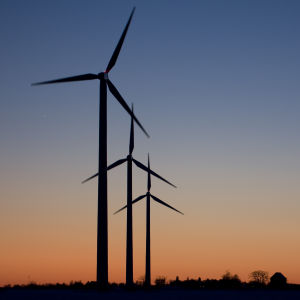 Tre vindkraftverk står mot en röd kvällshimmel.