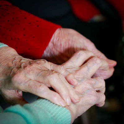 Två par äldre händer håller i varandra.