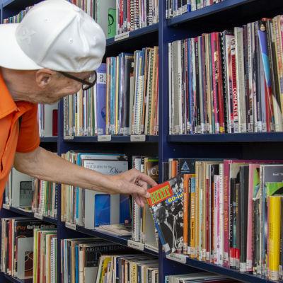 Mies tutkii levyjä kirjaston hyllystä