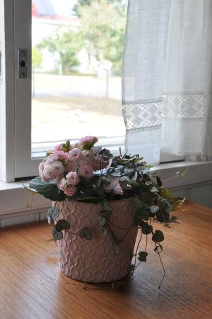 en blomma på ett bord vid ett fönster