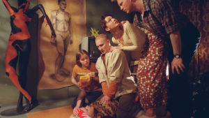 Nainen makaa maassa ja pitelee päätään. Mies painaa hänen rintakehäänsä ja kaksi muuta naista ja yksi mies seuraa tilannetta.