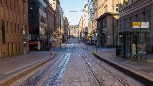 En öde gata, stenlagd, med spårvagnsskenor.