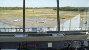 Bild tagen från flygledartornet på Helsingfors-Malms flygplats. Från fönstret ser man ett par småplan.