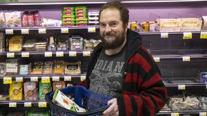 En man står framför kötthyllan i en mataffär. Han håller upp en butikskorg med varor i.