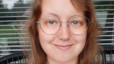 Ung kvinna med glasögon ler mot kameran.