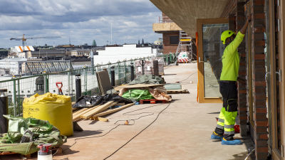 En byggarbetare på ett tak som håller på att byggas.