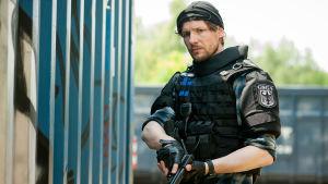 Poliisimies aseen kanssa.