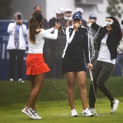 Kanssakilpailijat onnittelevat Matilda Castrenia LPGA-osakilpailun voitosta suihkuttamalla vettä hänen päälleen. Vieressä televisiokamera kuvaa iloista porukkaa.
