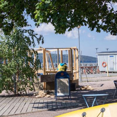 Keskellä kuvaa näkyy hamppusaunan ouiset tukirakenteet. Ympärillä Mukkulan rantaa ja kahvion tuoleja, taustalla järvi. Etualalla keltainen sup-lauta.