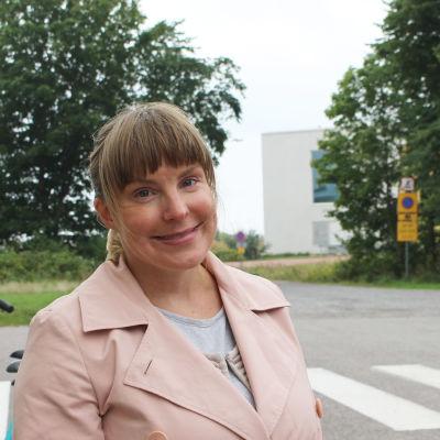 Kvinna i rosa jacka framför Fabriksudden