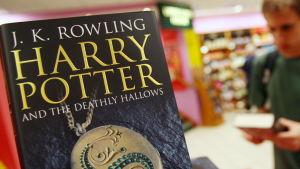 Boken Harry Potter and the deathly hallows i förgrunden, i en bokhandel som syns i bakgrunden.