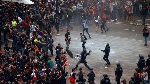 Demonstrationer vid den internationella flygplatsen El Prat i Barcelona. I bildens mitt syns en kravallpolis som motar ett slag mot en demonstrant.