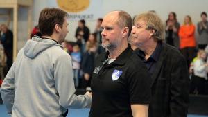 Chefstränaren Sebastian Freudenthal och lagledaren Stig Söderholm gratuleras av Karhut efter ligakvalet.