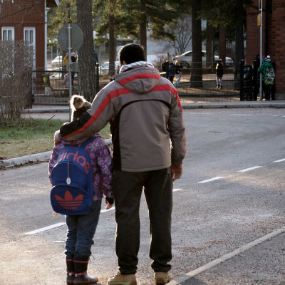Far håller arm om dotter, de står med ryggen till och ser på avstånd på en skola