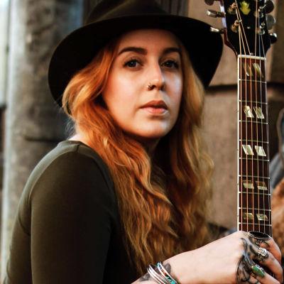 Mikaela Finne med sin akustiska gitarr.