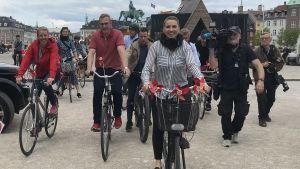 Mette Frederiksen cyklar med röda små flaggor fästa på cykelkorgen.