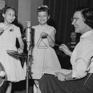 Perheen pienimmille -ohjelman juontaja Mirjami Suonio (Mirri-täti) ja Mirri-tädin Lyömäsoitinorkesteri studiossa vuonaa 1957.