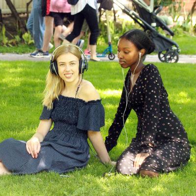 Två unga kvinnor lyssnar på ljuddramat Röster från pestens år.